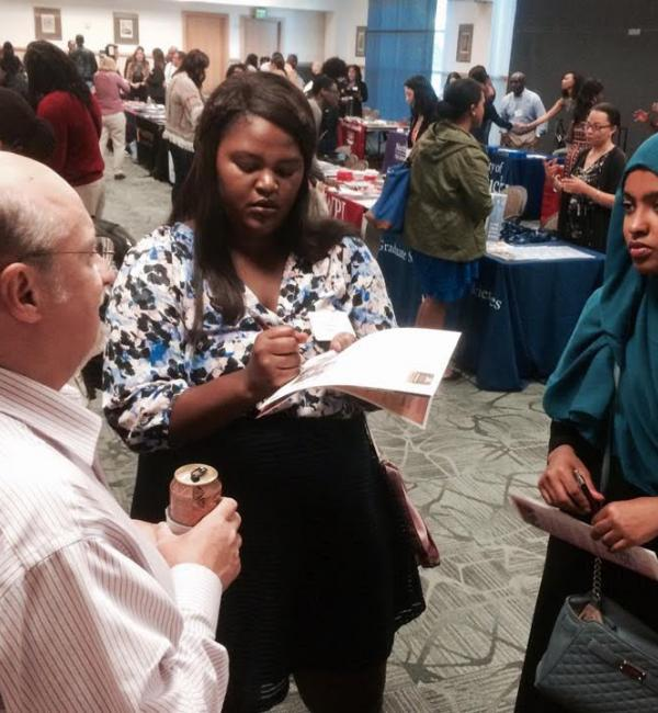 Three people talking at recruitment event